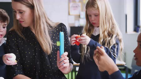 working together : Female teacher helping kids working with construction blocks in a primary school classroom, close up Stock Footage