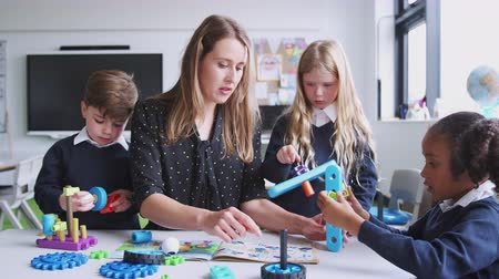 szelektív összpontosít : Female teacher helping kids working with construction blocks in a primary school classroom