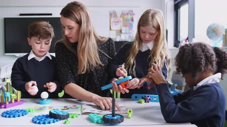 interessado : Female teacher helping kids working with construction blocks in a primary school classroom, close up Vídeos