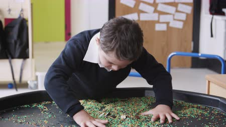 concentrando : Primary schoolboy with Down Syndrome stands using a sensory play tub in a classroom, close up