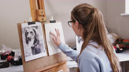 vászon : Female teenage artist drawing portrait of pet dog smudging charcoal - shot in slow motion
