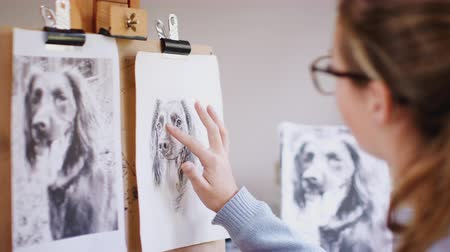 yoğunlaşma : Female teenage artist draws outline for portrait of pet dog in charcoal from photograph - shot in slow motion