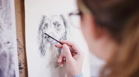 odstín : Female teenage artist draws portrait of pet dog in charcoal from photograph - shot in slow motion