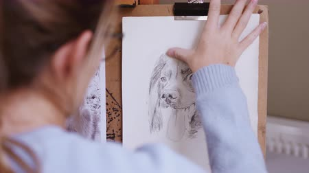 płótno : Female teenage artist drawing portrait of pet dog in charcoal using smudging technique - shot in slow motion