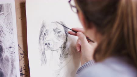 płótno : Close up of female artist working on portrait of dog in charcoal - shot in slow motion