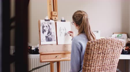 vászon : View through doorway as female teenage artist draws outline for portrait of pet dog in charcoal from photograph - shot in slow motion
