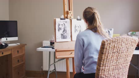 vászon : Rear view of female teenage artist drawing portrait of pet dog in charcoal from photograph - shot in slow motion