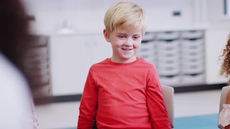 odaklanma : Young white schoolboy sitting in class listening to a story and gesturing, selective focus Stok Video