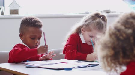 schoolbook : Young black schoolboy and classmates drawing at infant school art class, close up, selective focus