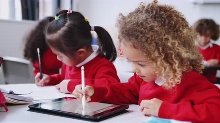 etnia africano : Two infant school kids sitting at a desk drawing with a tablet computer and stylus, close up