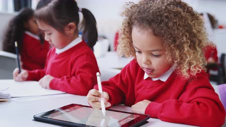 interessado : Young schoolgirl drawing with tablet computer in an infant school class, close up