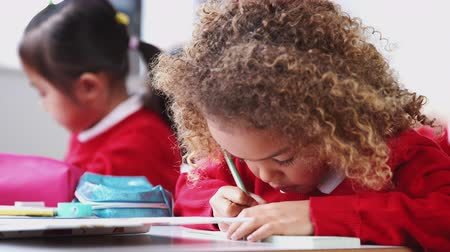 etnia africano : Young schoolgirl wearing school uniform sitting at desk in an infant school class drawing, close up