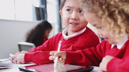 schoolkid : Two infant school girls drawing with tablet computer and stylus at a desk in class, close up