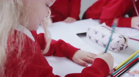 schoolbook : Young white schoolgirl drawing at desk in an infant school classroom, close up, over shoulder view Stock Footage