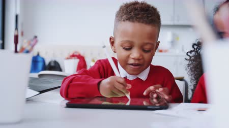 schoolkid : Young black schoolboy drawing using tablet computer and stylus in infant school, selective focus