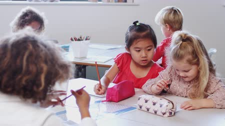 pré escolar : Two schoolgirls sitting at a desk with classmates in an infant school classroom working, close up Stock Footage