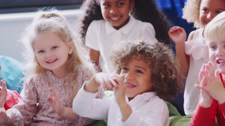 interessado : Infant school children in a comfortable corner of the classroom waving to their teacher, close up