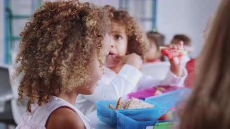 упакованный : Infant school girl at a table with classmates eating packed lunches, selective focus, close up