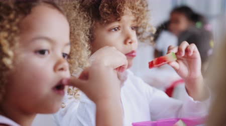rastrelliera : Close up of children eating their packed lunches together at infant school, rack focus