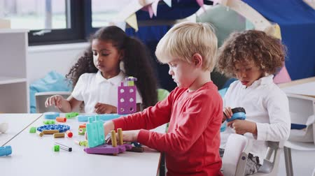 atenção : White infant school boy using educational construction toys with his classmates, close up