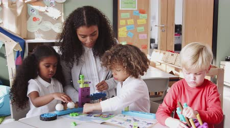 constructing : Female infant school teacher helping children using construction toys in classroom