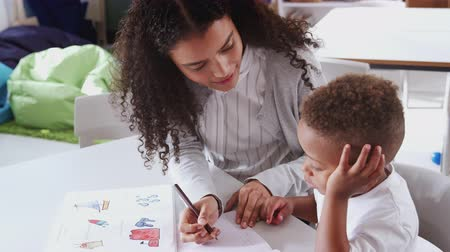 focus on foreground : Female infant school teacher working one on one with a young schoolboy in a classroom, elevated view Stock Footage