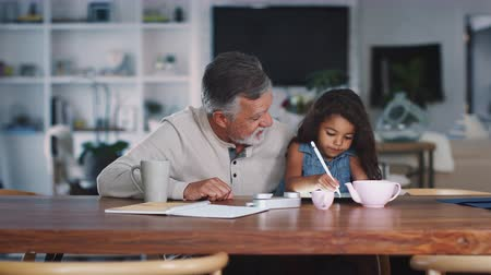 using stylus : Senior Hispanic man sitting with his granddaughter, who uses stylus and tablet computer, rack focus