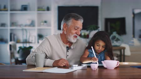 büszke : Senior Hispanic man talks with his granddaughter while she uses stylus and tablet computer, close up Stock mozgókép