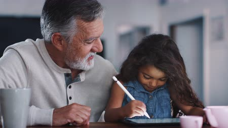 using stylus : Senior man talking with granddaughter while she uses stylus and tablet computer, close up, handheld