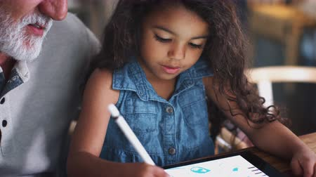 long hair : Close up of young girl drawing with tablet and stylus, with her grandfather sitting beside her Stock Footage