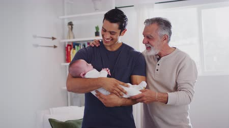 逆光 : Proud Hispanic father holding his four month old son at home, grandfather standing beside them 動画素材