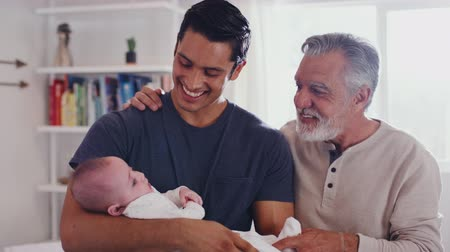beside : Proud Hispanic father holding his four month old son at home, with grandfather beside them, close up Stock Footage