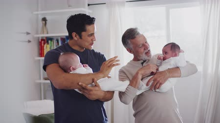 dvojčata : Young Hispanic man and his senior father holding his two baby boys at home, close up