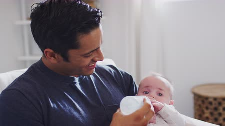 each other : Smiling Hispanic father sits rocking his four month old son, feeding him a bottle at home, close up