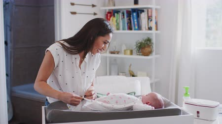 den matek : Happy mother changing the diaper of her newborn son at home on a baby changing table, waist up