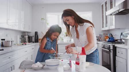 trouba : Jump cut clip of mother and young daughter preparing cake mix and baking cakes in their kitchen