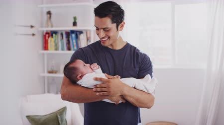 focus on foreground : Proud Hispanic father holding his four month old child at home, waist up, close up Stock Footage