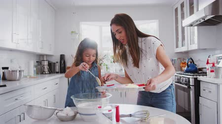 逆光 : Young girl putting cake mix into cake forms while baking with her mother in the kitchen, close up