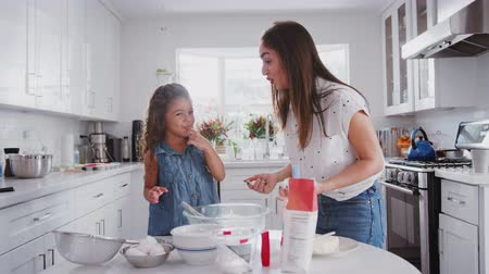 travessura : Young girl putting cake mix on her mum's nose while they bake together in the kitchen, close up