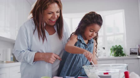 elliler : Young girl making cakes with her mum and grandmother filling cake forms with mix, close up, handheld Stok Video