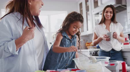 somente para adultos : Young girl making cakes with her mum and grandmother, close up, selective focus Stock Footage