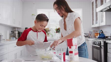 逆光 : Pre-teen Hispanic boy making cake mix in the kitchen with his mother, close up 動画素材