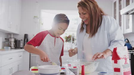 olhando para cima : Pre-teen boy and his grandmother making cakes in the kitchen, filling forms with cake mix, close up Stock Footage