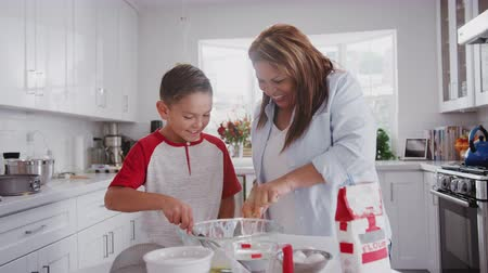 elliler : Pre-teen Hispanic boy and his grandmother making cakes in the kitchen, mixing cake mix, close up