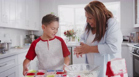 elliler : Happy pre-teen Hispanic boy and his grandmother baking cakes in kitchen high five and hug, close up Stok Video