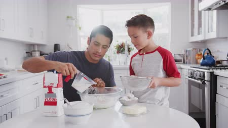 trouba : Jump cut clip of father and pre-teen son preparing cake mix and baking cakes in their kitchen