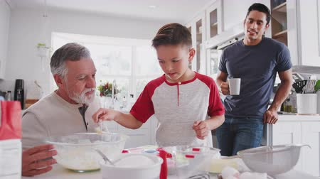 pré adolescente : Pre-teen Hispanic boy making cakes with his grandfather and father in the kitchen at home, close up Vídeos