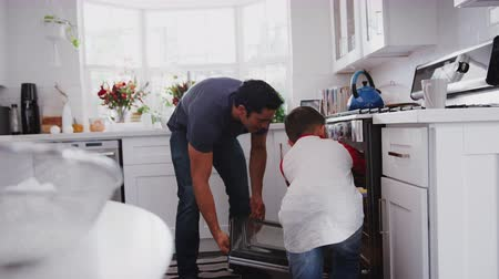 oven : Pre-teen Hispanic boy baking with grandfather and father in kitchen, putting cakes in oven, close up