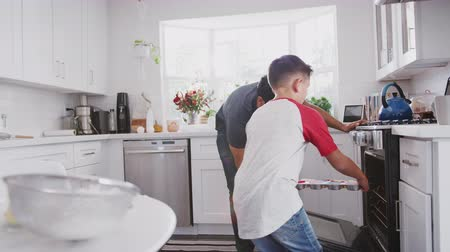trouba : Pre-teen Hispanic boy baking with his dad, high five and put cakes in the oven, close up