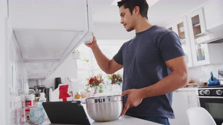 ângulo : Millennial man preparing cake mix following a recipe on a tablet computer, adding milk, close up